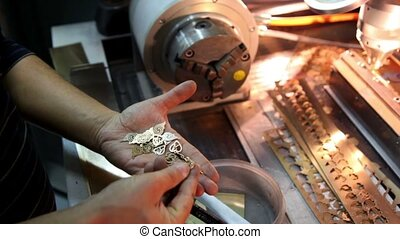 Handful of pendants lies in the palm, man sorting them -...