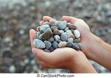 Handful of stones in hands, Against stones
