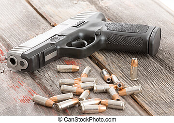 Handgun and a pile of scattered bullets lying on an old rustic wooden table conceptual of crime, violence, killing, coercion and protection of assets