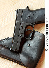 Handgun and holster - Modern automatic pistol and old...