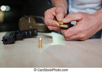 Metal handgun bullet being in hands of a man