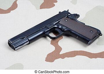 handgun on camouflage uniform