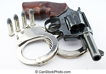 handgun revolver and police handcuff with bullets on white...