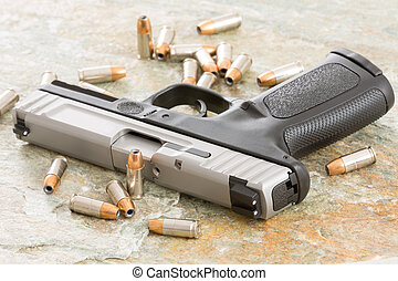 Handgun surrounded with scattered bullets littering the top of an old grungy wooden surface depicting crime, terrorism and violence or protection of personal assets