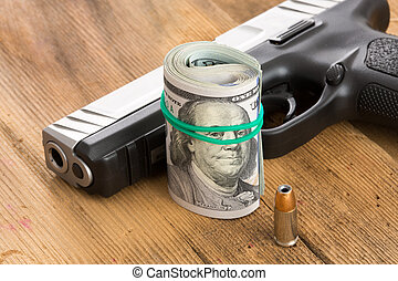 Handgun with a roll of dollar bills and a bullet