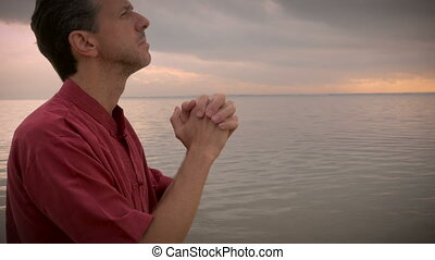 Handheld arch shot of man praying at the ocean as the sun...