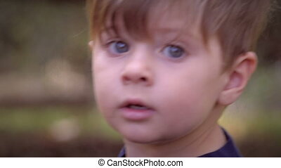 """""""An intimate close up portrait of a young little blond child looking and talking at the camera in slow motion. The child goes through a few different expressions including concern, happiness, worry, and joy."""""""