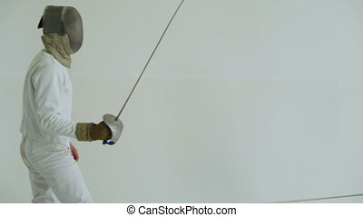 Handheld of Two fencers have fencing training on white...