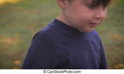 Handheld of young boy is turning his back to the camera and...
