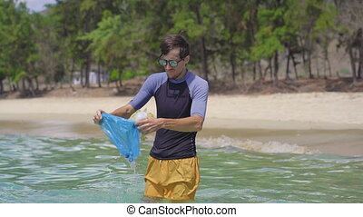 Handheld shot of a man that collects plastic bags in the beautiful turquoise sea. Paradise beach pollution. The problem of garbage on the beach sand caused by man-made pollution. Eco campaigns to clean the environment. Ecological volunteering concept