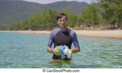 Handheld shot of a man that collects plastic bags in the beautiful turquoise sea. Paradise beach pollution. The problem of garbage on the beach sand caused by man-made pollution. Eco campaigns to clean the environment. Ecological volunteering concept.