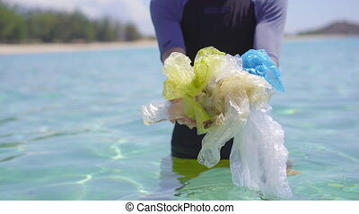 Handheld shot of a man that collects plastic bags in the ...