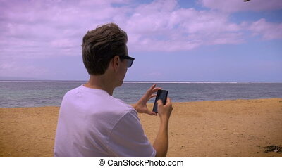 Handheld shot of tourist man on beach taking photos with his phone