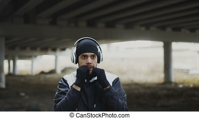 Handheld shot of Young man boxer in headphones training...