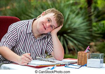 Handicapped boy resting on hand at desk. - Close up portrait...