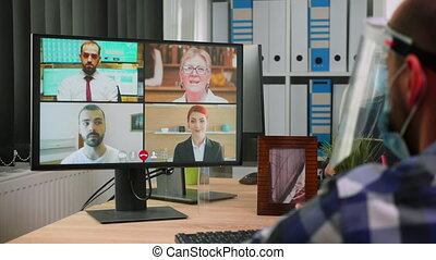 Back view of business man in wheelchair talking to colleagues about plan in video conference wearing visor in new normal office. Immobilized freelancer working in company respecting social distance