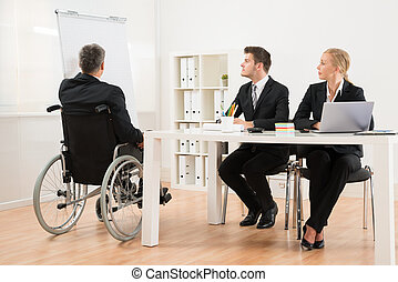 Handicapped Businessman Explaining To His Colleagues