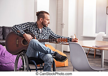 Handicapped creative man writing down new song
