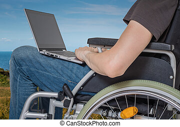 Handicapped disabled man on wheelchair is working with laptop ou
