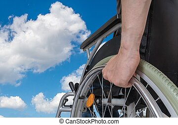 Handicapped disabled man sitting on wheelchair against blue sky.