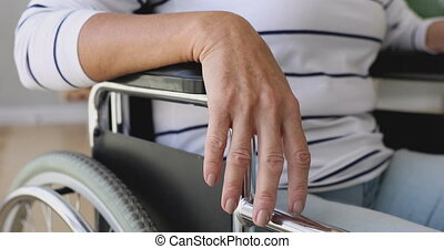 Handicapped disabled old woman sit on wheelchair, close up view