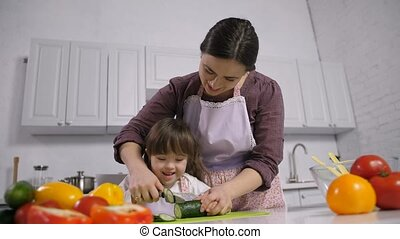 Handicapped down syndrome child with mother cooking - Joyful...