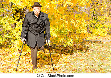 Handicapped elderly male amputee in a fall park taking a...