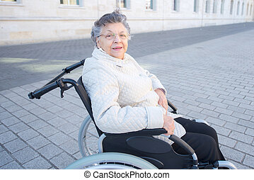 handicapped elderly woman sitting in a wheelchair outdoor