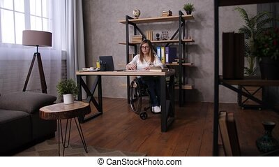 Focused female with differing abilities in wheelchair working with drawings on paper in home office. Positive woman with impaired mobility scratching cat pet with pencil while making drawing at table