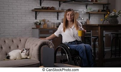 Self-employed woman with differing abilities moving around domestic room in wheelchair while taking break during work at laptop. Disabled female drinking coffee, stroking cat while teleworking at home