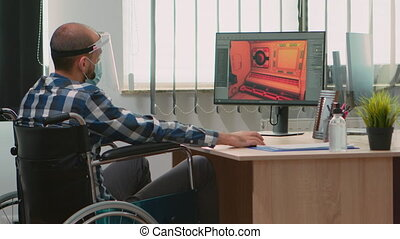 Handicapped game developer sitting in wheelchair with protection mask working at new project from new normal studio office during covid-19 pandemic. Immobilized man respecting social distance.