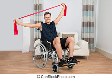 Handicapped Man On Wheelchair Exercising With Resistance Band