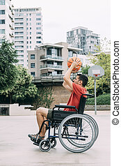 handicapped man playing basketball in the city