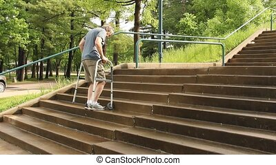 handicapped man uses a walker to climb a set of stairs