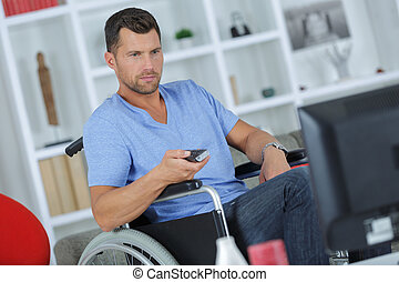 handicapped man using remote control while watching television
