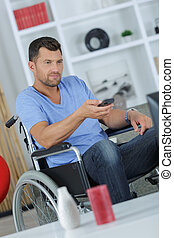 handicapped man watching television in living room