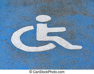 Handicapped or disabled parking sign on blue asphalt