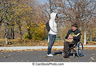 Handicapped senior man in a wheelchair outdoors
