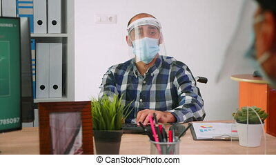 Handicapped businessman with visor and protection mask discussing with colleague working in new normal business office. Man respecting social distance in financial company during global pandemic.