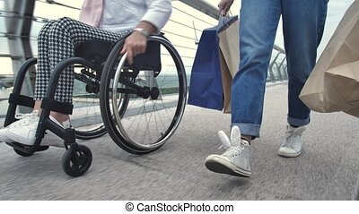 Low section of disabled female on wheelchair riding next to her daugher walking holding shopping bags. Mother with differing abilities and girl with paper bags walking after shopping, close-up of legs