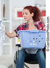 handicapped woman sitting in wheelchair doing her laundry at home
