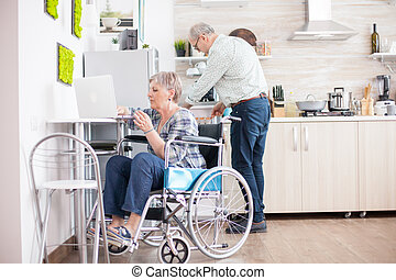 Handicapped woman typing on laptop in the kitchen. Disabled old woman in wheelchair working. Paralyzed handicapped old elderly person using modern communication online internet web techonolgy.