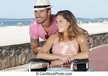handicapped young couple resting on a beach
