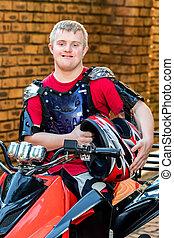 Handicapped young quad bike rider holding helmet.