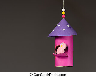 Handicraft of a colorful bird house and a small bird made of...