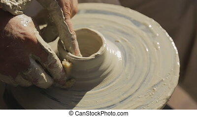Handicraftsman labors on creation of pottery on Potter's wheel.