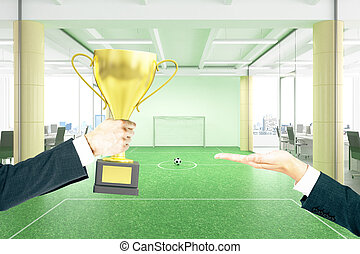 Handing trophy football field