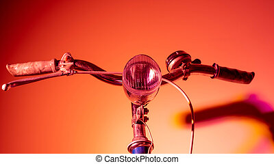 Handlebar with headlight from an old isolated bicycle on a coloured background. Vintage concept. Neon lights