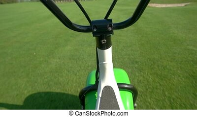 Handlebars and grass background. Electric scooter moving....
