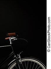 handlebars and wheel of vintage bicycle isolated on black